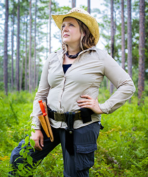 Woman with straw cowboy hat and casual clothes in a forest with toolbelt