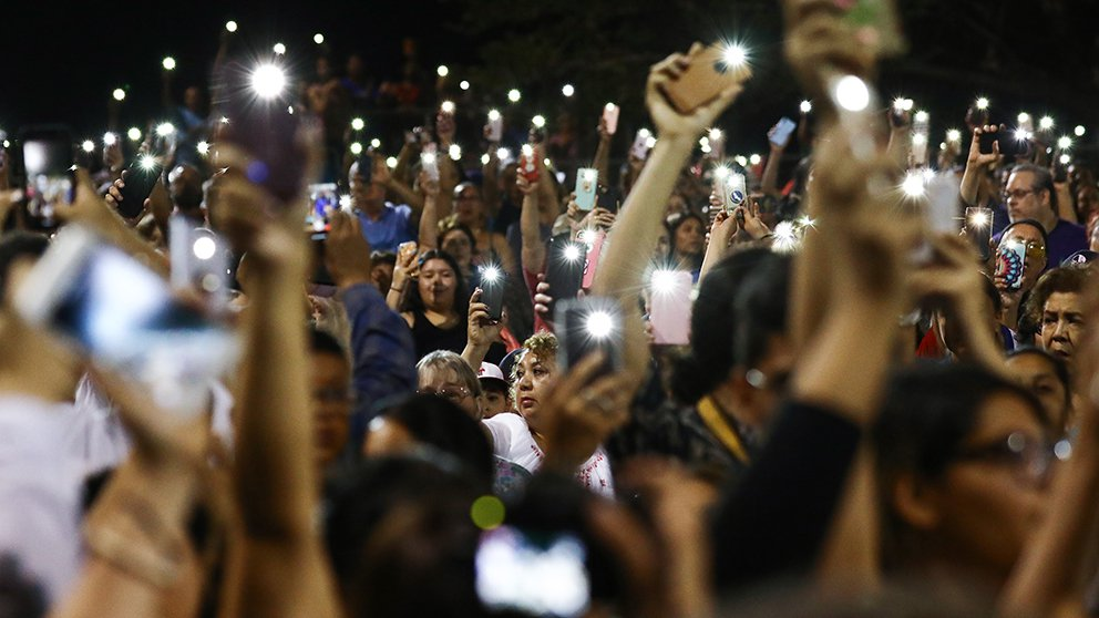 crowd in evening light with cell phones raised as lights
