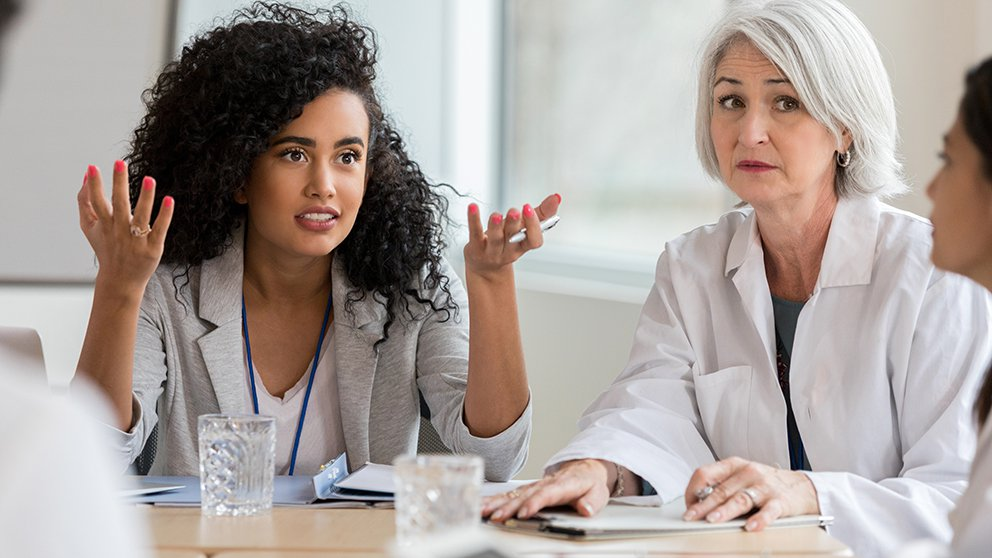 older white woman in white coat and younger black woman in suit speaking with third woman facing away