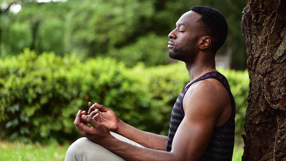 Young black man in meditation position under a tree