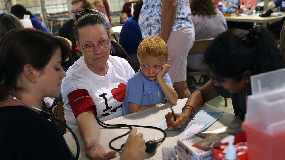 Woman getting blood pressure checked while holding son in her lap.