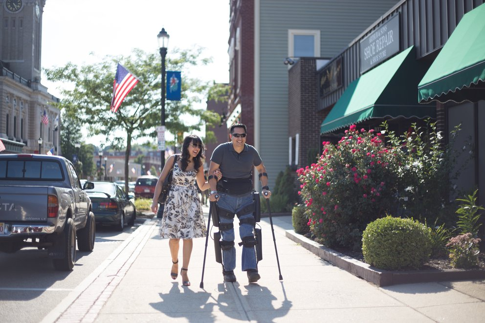 Man with exoskeleton walking with woman