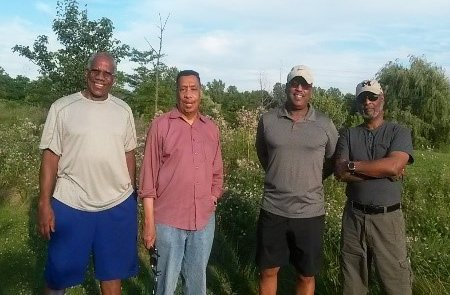Four black men in casual clothing in a country setting