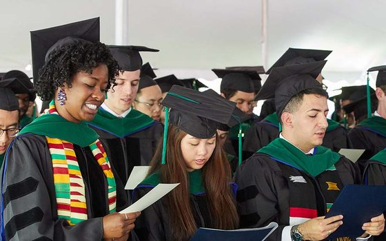 A group of medical school students are standing up, dressed in graduation caps and gowns, and reciting a medical oath. The photo focuses on four students.