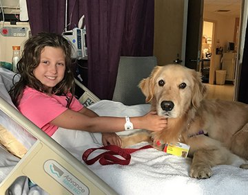 Smiling girl in hospital bed with dog next to her