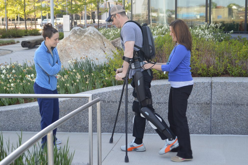 Two women assist man with crutches & exoskeleton