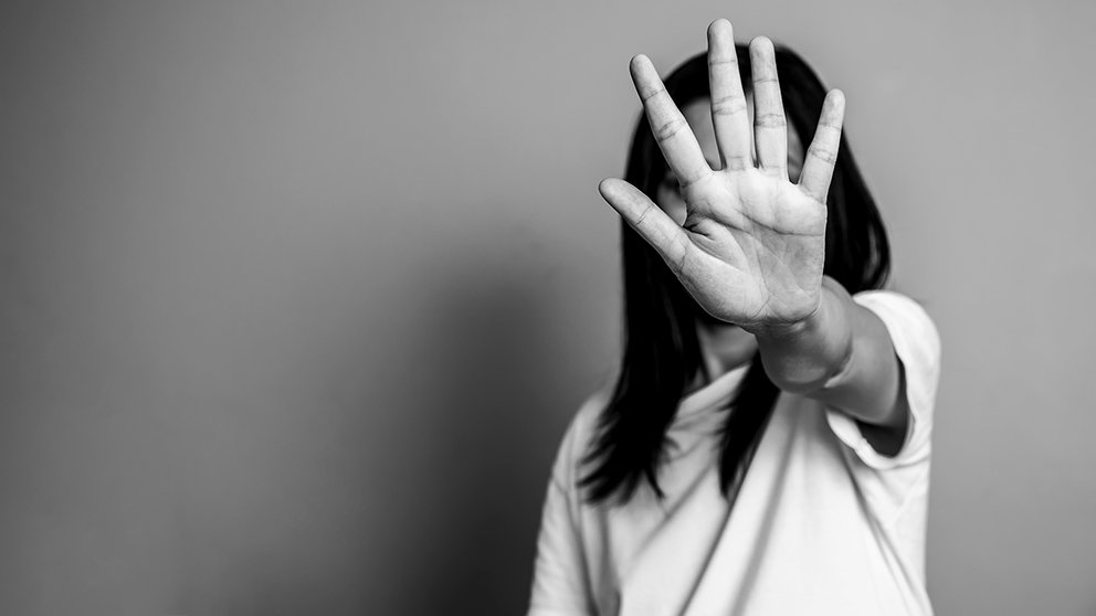 Black and white photo of woman holding a hand in front of her face in a defensive gesture