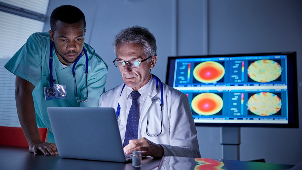 older white man in white coat and younger black man in scrubs looking at laptop with computer scans in background